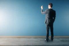Uomo d'affari che attinge parete blu Fotografia Stock Libera da Diritti