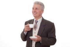 Uomo d'affari che beve da una tazza su un bianco Immagini Stock
