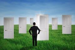 Uomo d'affari che cammina alle porte di opportunità Immagini Stock