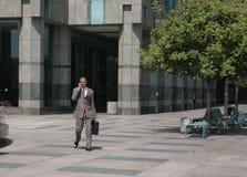 Uomo d'affari che cammina attraverso il cortile Fotografia Stock Libera da Diritti