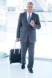 Uomo d'affari che cammina con i bagagli e che per mezzo del suo smartphone Immagine Stock