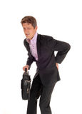 Uomo d'affari che cammina con il dolore alla schiena Fotografia Stock