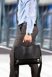 Uomo d'affari che cammina e che tiene una cartella di cuoio nel suo Han Fotografia Stock