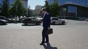 Uomo d'affari che cammina nella via per lavorare Movimento lento video d archivio