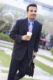 Uomo d'affari che cammina per funzionare con caffè Immagine Stock Libera da Diritti