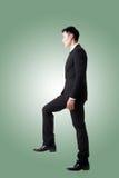 Uomo d'affari che cammina su sulle scale fotografia stock libera da diritti
