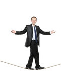 Uomo d'affari che cammina su una corda Fotografia Stock