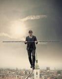 Uomo d'affari che cammina su una corda immagini stock