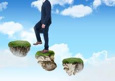 Uomo d'affari che cammina sui punti delle piattaforme di galleggiamento della roccia in cielo Immagine Stock Libera da Diritti