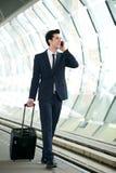 Uomo d'affari che cammina sul binario della stazione ferroviaria e che parla sul telefono Fotografia Stock
