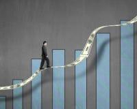 Uomo d'affari che cammina sulla tendenza dei soldi di crescita con il grafico Fotografie Stock Libere da Diritti