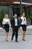 Uomo d'affari che cammina sulla via con i loro segretari Immagini Stock