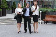 Uomo d'affari che cammina sulla via con i loro segretari Fotografie Stock