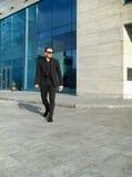 Uomo d'affari che cammina sulla via vicino all'ufficio Fotografia Stock
