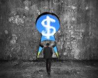Uomo d'affari che cammina verso la porta del buco della serratura con la nuvola v del simbolo di dollaro Immagini Stock Libere da Diritti