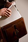 Uomo d'affari che cattura il computer portatile del uot dal caso Immagine Stock Libera da Diritti