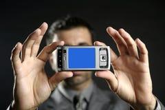 Uomo d'affari che cattura le foto, macchina fotografica mobile fotografia stock