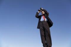 Uomo d'affari che cerca con il suo binocolo Immagine Stock