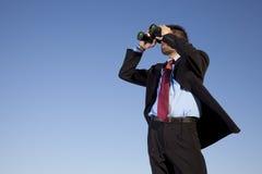 Uomo d'affari che cerca con il suo binocolo Fotografia Stock