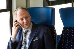 Uomo d'affari che chiama da un treno fotografia stock