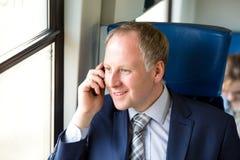 Uomo d'affari che chiama da un treno fotografie stock