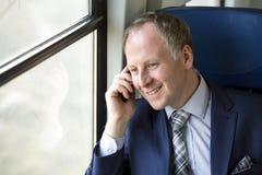 Uomo d'affari che chiama da un treno Immagine Stock
