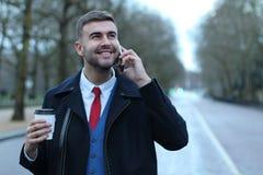 Uomo d'affari che chiama dal telefono sulla strada vuota Immagine Stock