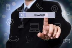 Uomo d'affari che clicca il campo di ricerca con le parole chiavi immagini stock