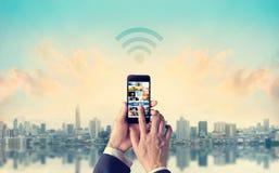 Uomo d'affari che collega i pagamenti mobili alla rete di Wifi in ci Fotografie Stock Libere da Diritti