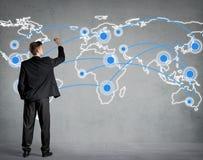 Uomo d'affari che collega i punti su una mappa di mondo Immagini Stock Libere da Diritti
