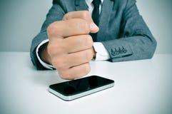 Uomo d'affari che colpisce uno smartphone con il suo pugno Fotografia Stock