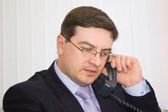 Uomo d'affari che comunica sul telefono Fotografia Stock