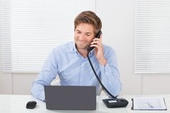 Uomo d'affari che comunica sul telefono della linea terrestre Immagini Stock Libere da Diritti