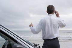 Uomo d'affari che comunica sul telefono delle cellule al mare Fotografie Stock