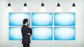 Uomo d'affari che considera i sei schermi in bianco della TV Immagini Stock