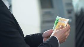 Uomo d'affari che conta gli euro che vuole inviare alla famiglia, trasferimenti di denaro rapidi stock footage