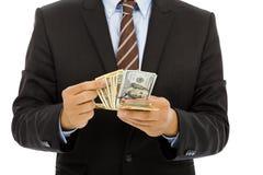 Uomo d'affari che conta i dollari americani con fondo bianco Immagini Stock