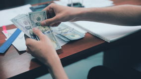 Uomo d'affari che conta i dollari e che controlla i risultati finanziari archivi video