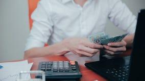 Uomo d'affari che conta i dollari e che controlla i risultati finanziari stock footage