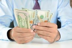 Uomo d'affari che conta soldi, banconote del dollaro americano (USD) fotografia stock