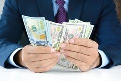 Uomo d'affari che conta soldi, fatture del dollaro americano (USD) fotografie stock libere da diritti