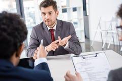 Uomo d'affari che conta sulle dita durante l'intervista di lavoro Immagini Stock