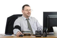 Uomo d'affari che controlla la sua pressione sanguigna davanti al monitor Immagine Stock