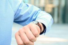 Uomo d'affari che controlla tempo sul suo orologio vicino con l'ufficio Immagini Stock