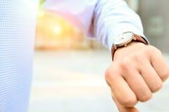 Uomo d'affari che controlla tempo sul suo orologio vicino con l'ufficio Fotografie Stock