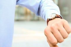 Uomo d'affari che controlla tempo sul suo orologio vicino con l'ufficio Fotografia Stock Libera da Diritti