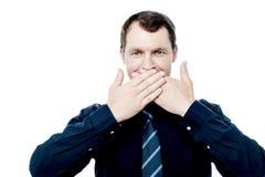 Uomo d'affari che copre il suo bocca di mani Fotografie Stock Libere da Diritti