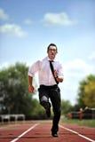 Uomo d'affari che corre velocemente sulla pista atletica nel concetto di urgenza e di stress da lavoro Fotografie Stock