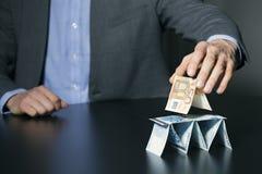 Uomo d'affari che costruisce piramide finanziaria da euro soldi Fotografia Stock Libera da Diritti
