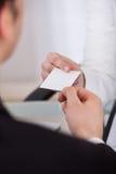 Uomo d'affari che dà biglietto da visita al collega allo scrittorio Immagine Stock Libera da Diritti
